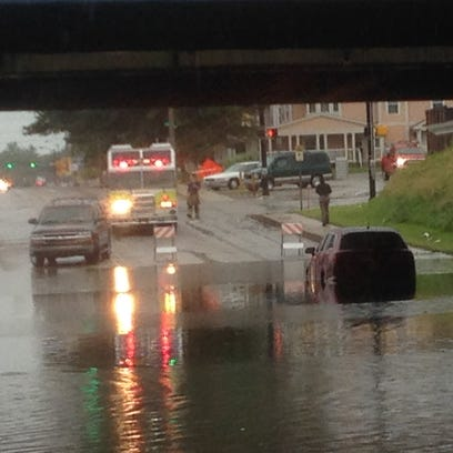 Rescue crews help a driver stuck in flooding in the