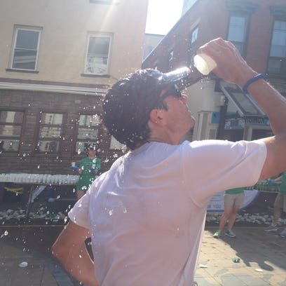 A competitor dumps water on his face on Church Street