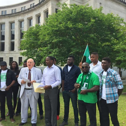 A group of Nigerian students and their attorneys gather