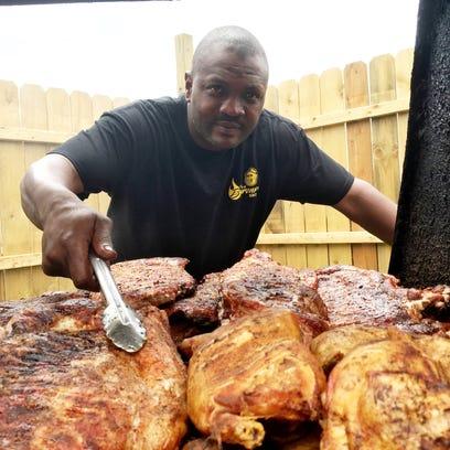 Byron McMorris turns pork ribs and chicken on his smoker