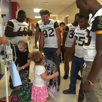 A group of Southern Miss football players visit with