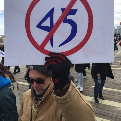 A protester holds a sign Saturday, Feb. 17, with a