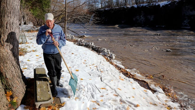 Tom Kozaczka walks in his yard along the rushing Cazenovia Creek on Monday, Nov. 24, 2014, in West Seneca, N.Y. Western New York is preparing for potential flooding from melting snow following last week's snowstorms. (AP Photo/Mike Groll)