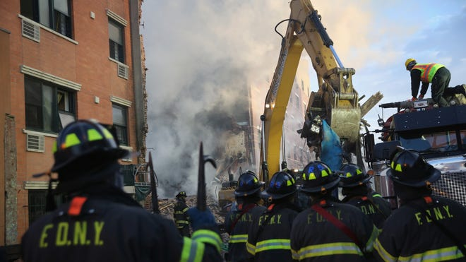 Firemen watch as work crews remove debris from the smoking site of an explosion in East Harlem on March 13 in New York City. At least eight people were killed in Wednesday's explosion that collapsed two buildings on Park Avenue at East 116th Street.