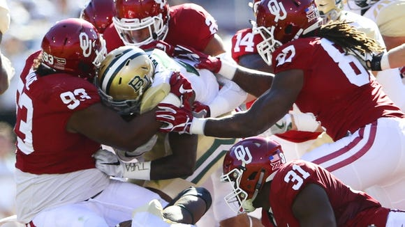 Baylor Bears running back Terence Williams (22) is tackled by Oklahoma Sooners defensive tackle Jordan Wade (93) and linebacker Ogbonnia Okoronkwo (31) during the first quarter at Gaylord Family - Oklahoma Memorial Stadium.on Nov 12, 2016.