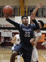 Redwood's Kobe Garner goes in for a layup against a Mt. Whitney defender during the first half of their West Yosemite League basketball game Wednesday, Feb. 15, 2017 in Visalia, Calif.