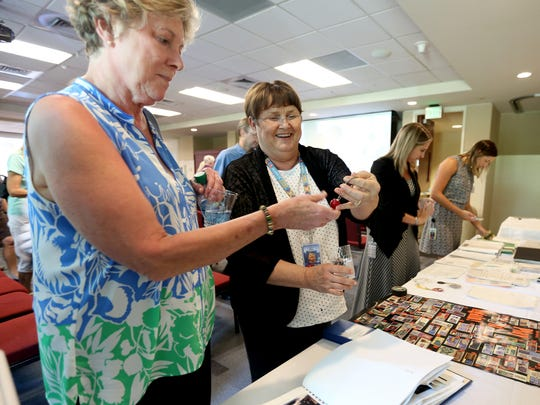LeeAnn Reece, left, a retired Oregon Lottery employee, and Carol Floyd, a customer service representative, look through items found in a 20-year-old time capsule on Monday, Sept. 12, 2016. Floyd was one of the original people to decide what would be included in the capsule when it was sealed in 1996.