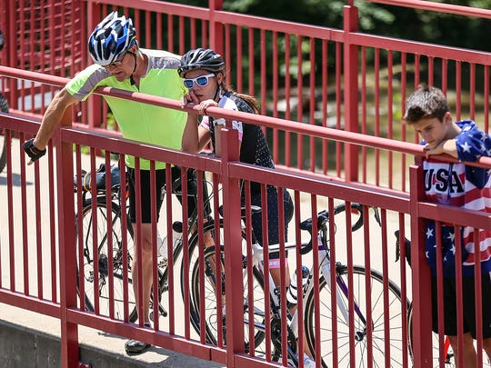 """Cyclists and pedestrians stop along the Monon Trail, viewing the remnants of a water rescue near the Broad Ripple dam of the White River at Westfield Boulevard and 72nd Street, where the river passes below the Monon Trail in Indianapolis, Sunday, July 9, 2017. Two kayakers were in critical condition after being rescued from the """"boil,"""" a rapid churning area of the low-head dam. The force of the water pulled off the life vests that both kayakers had been wearing."""