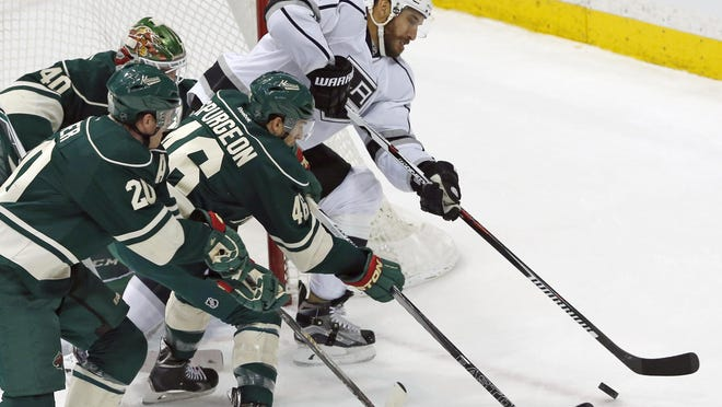 The Minnesota Wild's Ryan Suter, left, and Jared Spurgeon pursue the puck with Los Angeles Kings' Dwight King, right, in the first period Tuesday in St. Paul.