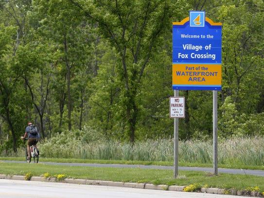A biker rides south along County CB into the Village