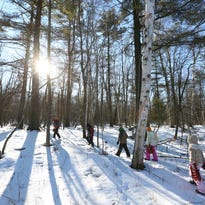 Kids from Woodland Dunes Nature Center and Preserve's Kids' Nature Club follow bunny tracks into the woods on Thursday, Feb. 11 in Two Rivers. The club, which is open to the public, meets once a month for nature walks and different activities.