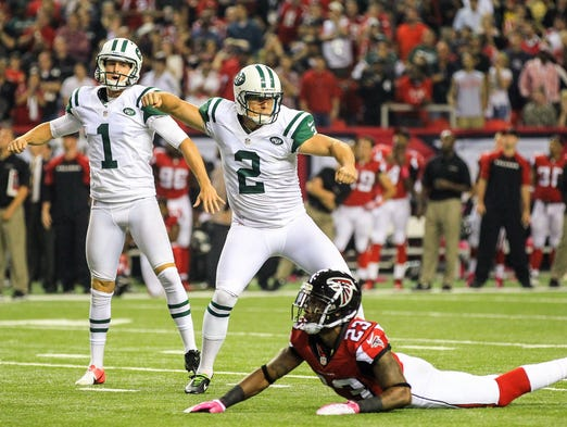 New York Jets place kicker Nick Folk (2) celebrates the game winning field goal kick in the second half against the Atlanta Falcons at the Georgia Dome. The Jets won 30-28.