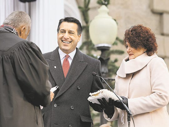 In this Jan. 3, 2011 file photo, Nevada Gov. Brian Sandoval, with wife Kathleen, takes the oath of office from Chief Supreme Court Justice Michael Douglas at the Capitol in Carson City, Nev.