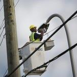 A Detroit Public Lighting Department crew maintains street lights on Warren Avenue in Detroit on Oct. 14, 2013.