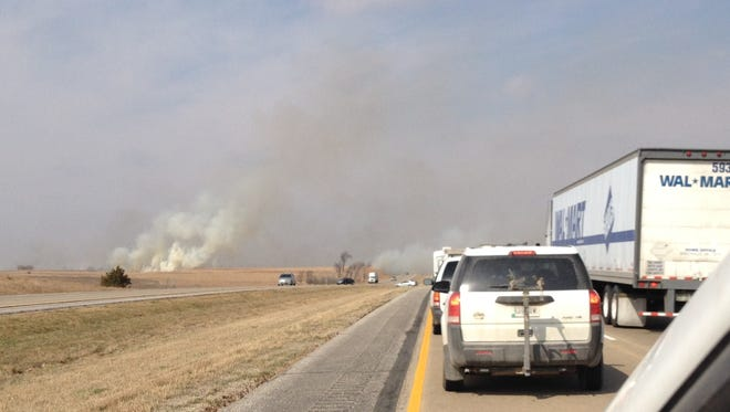 A grass fire burns on Highway Interstate 80 west of Adair on Saturday morning.