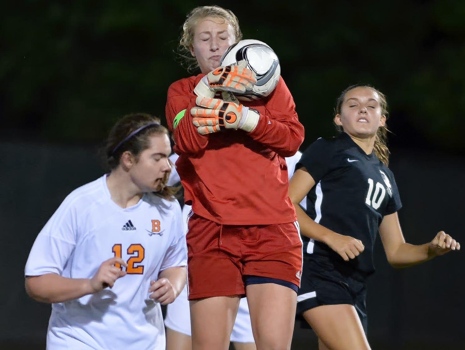 Beech High senior goalkeeper Allie Guinn leaps to gain possession in front of sophomore teammate Sierra Robinson (12) and Station Camp junior McKenzie Polk.