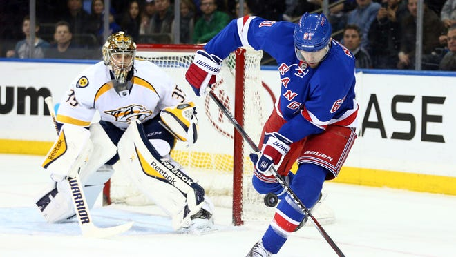 New York Rangers left wing Rick Nash (61) tries to gain control of the puck in front of Nashville Predators goalie Pekka Rinne (35) during the second period at Madison Square Garden.