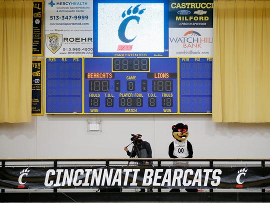 The UC Bearcats stands with a camera man on the elevated mezzanine during the fourth quarter of the NCAA women's basketball game between the Cincinnati Bearcats and the Southeastern Louisiana Lions at St. Ursula Academy in the East Walnut Hills neighborhood of Cincinnati on Wednesday, Nov. 15, 2017.