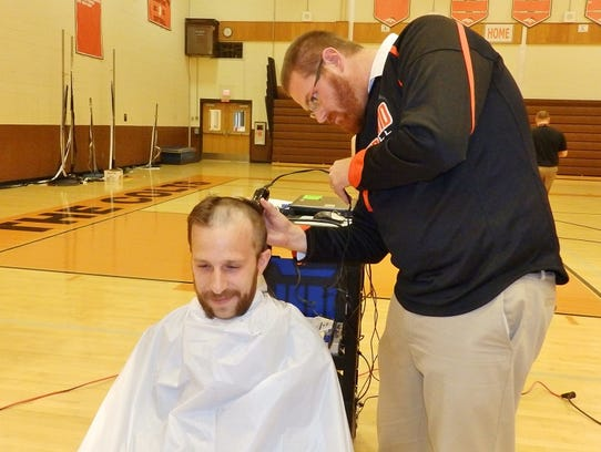 Gene Thomas shaves the head of Matthew Evans, following