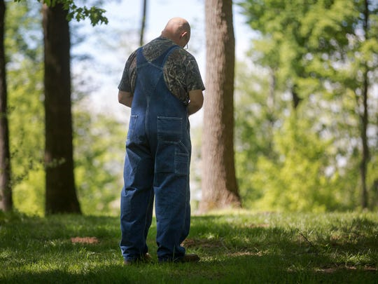 Jim 'Slim' Pieniazek, of Steubenville, stands over his son's grave at Spring Grove Cemetery and Arboretum on the first anniversary of his death.