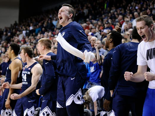 The BYU bench celebrates a basket against Gonzaga during