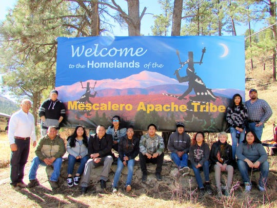 Art students from Marty Lane's class at the Mescalero School sit underneath the new sign they designed. School Supt. Charlie Sevedra said the students also will cover the other billboards located near the sawmill, Casino Apache Travel Center and on New Mexico Highway 244 near Cloudcroft.