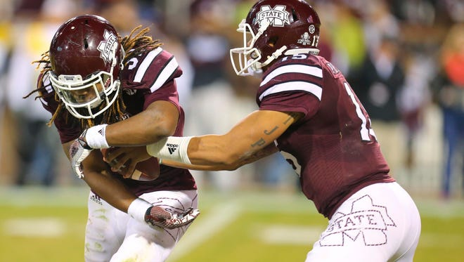 Nov 22, 2014; Starkville, MS, USA; Mississippi State Bulldogs quarterback Dak Prescott (15) fakes a handoff to running back Ashton Shumpert (32) during the game against Vanderbilt at Davis Wade Stadium.   Mandatory Credit: Spruce Derden-USA TODAY Sports