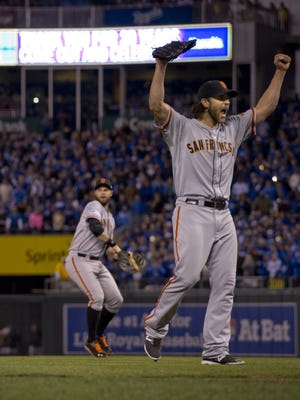 San Francisco Giants pitcher Madison Bumgarner raises his arms after the final out in the ninth inning against the Kansas City Royals in Game 7 of the World Series on Wednesday, Oct. 29, 2014, at Kauffman Stadium in Kansas City, Mo. The Giants won, 3-2, to capture the Series title.