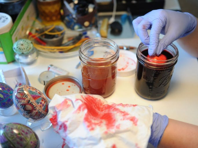 Jordan Byrd dips a goose egg in its first round of dye while practicing the art of pysanky, or Ukrainian egg decorating, in her Knoxville home on Tuesday, March 15, 2016.