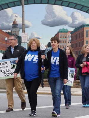 """Kathy Scott and Shelly Crall share the honors of carrying the torch Wednesday morning at the square in Bucyrus during the """"Torch Run for Life"""" event to raise awareness for organ, eye and tissue donation."""