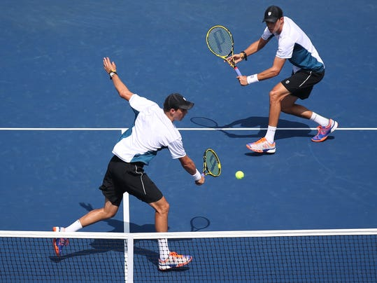 Mike Bryan, left, returns a shot as Bob Bryan looks on during a doubles match against Bradley Klahn, and Tim Smyczek, during the third round of the 2014 U.S. Open tennis tournament, Monday, Sept. 1, 2014, in New York. (AP Photo/John Minchillo)