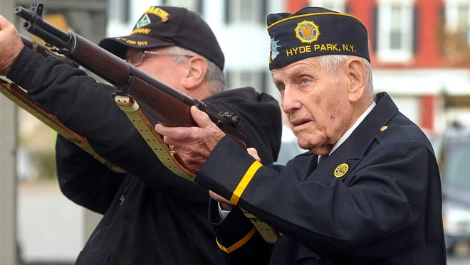 Above, Ernie Trautman, right, of Hyde Park honors those who served Tuesday with a six-gun salute.