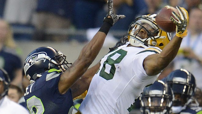 Green Bay Packers receiver Randall Cobb (18) tries to make a one-handed catch past Seattle Seahawks cornerback Marcus Burley (28) during their Week 1 game at CenturyLink Field in Seattle.
