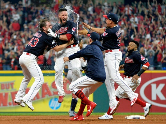 Cleveland Indians' Yan Gomes, second from left, hit a game winning RBI-single in the 13th inning of Game 2 of baseball's American League Division Series against the New York Yankees, Friday, Oct. 6, 2017, in Cleveland.