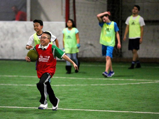 Corazon Barocio, 17, runs the ball back to the center circle while celebrating scoring a goal during a youth soccer program with North Salem High School's boys soccer team, Wednesday, November 18, 2015, at Salem Indoor Soccer Center in Salem, Ore.