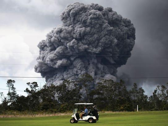 A man drives a golf cart at a golf course as an ash