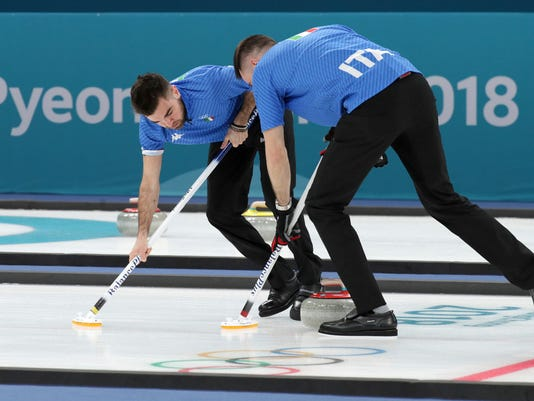 Italy's Simone Gonin, left, sweeps ice with teammates sweep ice during their men's curling match against Britain at the 2018 Winter Olympics in Gangneung, South Korea, Sunday, Feb. 18, 2018. (AP Photo/Aaron Favila)
