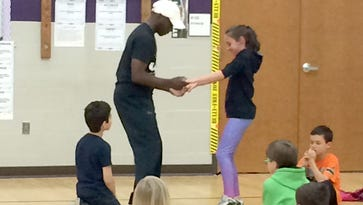 Anna Lehman, a third grade student at Dillsburg Elementary, and Jason Reed, resident artist and professional dancer, demonstrate basic steps in Latin partner dance to a third grade audience at Dillsburg Elementary.