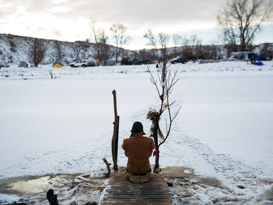 Army veteran Nick Biernacki, of Indiana, prays at the Cannonball River at the Oceti Sakowin camp where people have gathered to protest the Dakota Access oil pipeline in Cannon Ball, N.D., Sunday, Dec. 4, 2016. Tribal elders have asked the military veterans joining the large Dakota Access pipeline protest encampment not to have confrontations with law enforcement officials, an organizer with Veterans Stand for Standing Rock said Sunday, adding the group is there to help out those who've dug in against the four-state, $3.8 billion project.