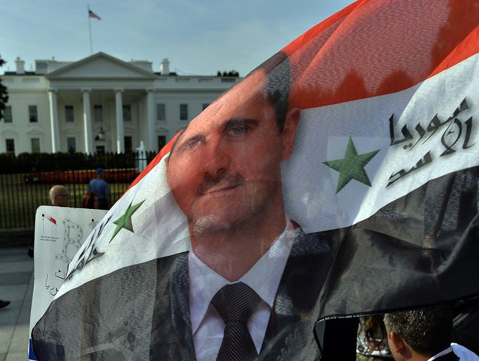 Supporters of Syrian President Bashar Assad wave a Syrian national flag in front of the White House on Sept. 9 in Washington, D.C.