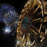Fair goers enjoy the rides during the fireworks display at Carnival Americana, part of the Larimer County Fair & Rodeo Friday night August 2, 2013.