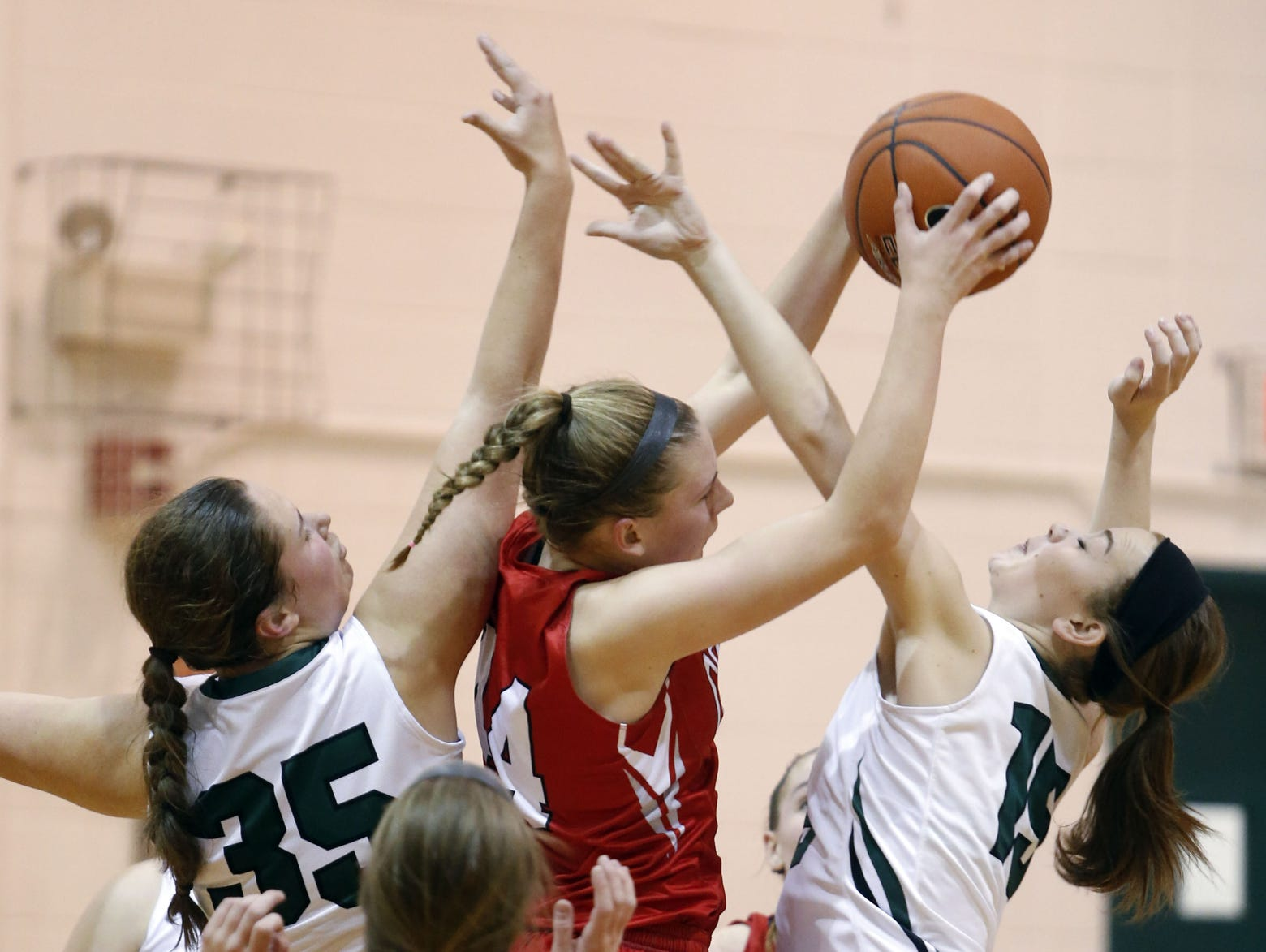 Conrad's Stefanie Kulesza reaches for a rebound between Archmere's Amanda Denning (left) and Sydney Niumataiwalu in the first half of Conrad's 45-44 win Tuesday.