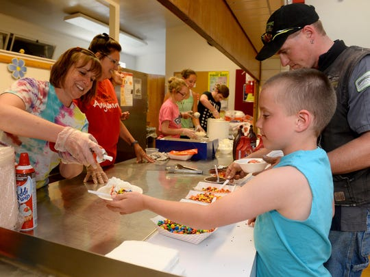 Noah Pozder loads up on whipped cream during the Lincoln Elementary School Ice Cream Social and Book Fair.