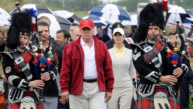 Donald Trump, center, is seen escorted by Scottish pipers as he officially opens his new multi-million pound Trump International Golf Links course in Aberdeenshire, Scotland, in 2012.