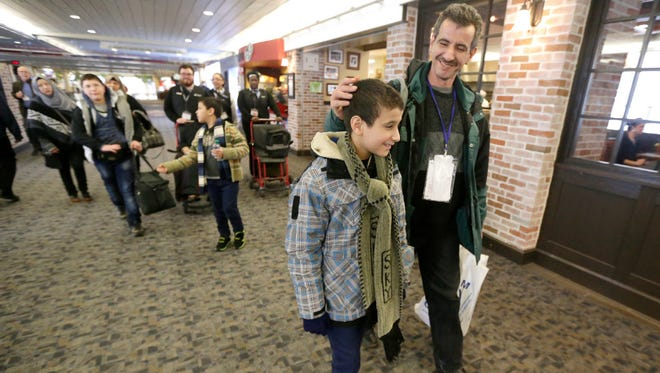 Saeed Sofan walks with his son Hamza Sofan, 11, through the terminal with other family members behind as they head to baggage claim shortly after arriving at Mitchell International Airport in Milwaukee on Wednesday.