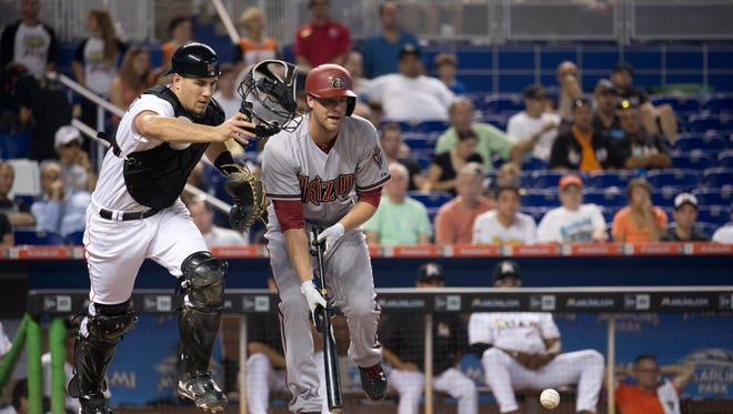 Miami Marlins catcher J.T. Realmuto (20) chases a foul ball after Arizona Diamondbacks' Archie Bradley (25) bunted during the second inning of a baseball game in Miami, Thursday, May 21, 2015. He bunted out with two on base.