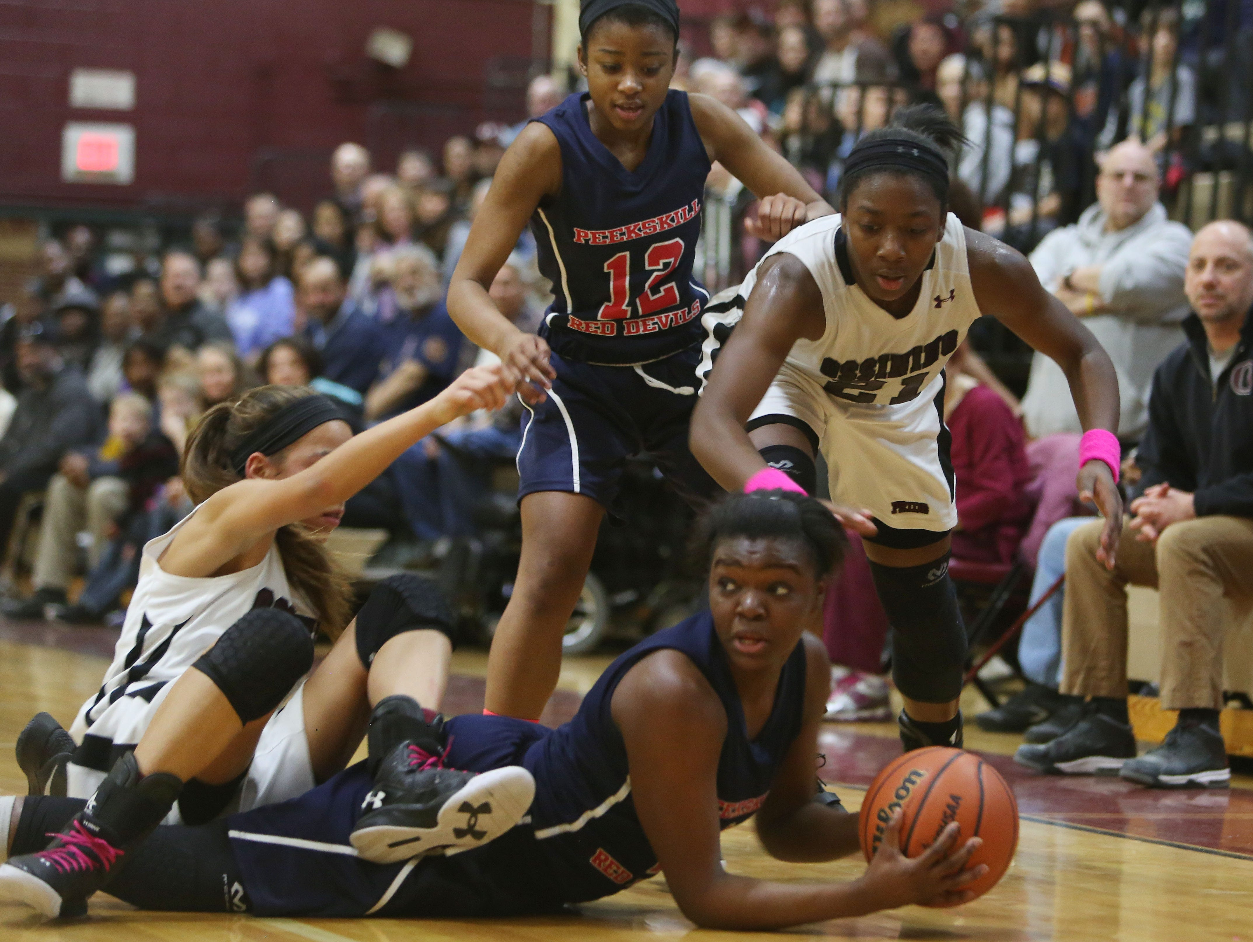 Peekskill's Lanay Rodney (1) looks for a teammate while getting pressure from Ossining's Jaida Strippoli (4) and Shadden Samuels (21) during girls basketball game at Ossining High School Feb. 2, 2016.