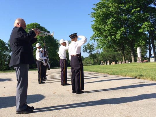David Ehren sounds taps while the squad from American Legion Post 262 stands at attention Monday in a Memorial Day ceremony at St. Joseph Cemetery in Champion.