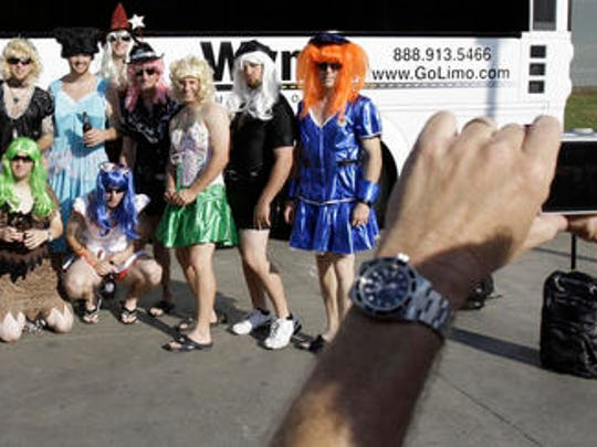 FILE - In this Sept. 24, 2008, file photo, Oakland Athletics rookie players dressed in costumes line up for a group photo before boarding the team bus after their 14-4 loss to the Texas Rangers, in Arlington, Texas. That hazing ritual of dressing up rookies as Wonder Woman, Hooters Girls and Dallas Cowboys cheerleaders is now banned. Major League Baseball created an Anti-Hazing and Anti-Bullying Policy that covers the practice. As part of the sport's new labor deal, set to be ratified by both sides Tuesday, Dec. 12, 2016 the players' union agreed not to contest it.
