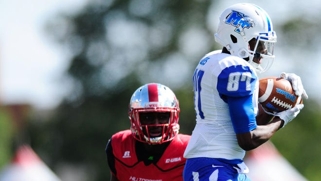 MTSU wide receiver Richie James (87) makes a catch over Western Kentucky defensive back Marcus Ward earlier this season.